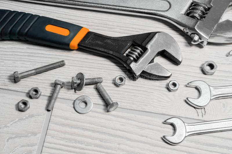 Adjustable spanners and wrenches, nuts and bolts on the table. Adjustable spanners and ordinary wrenches, nuts and bolts are on the table close up stock images