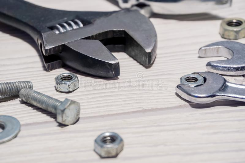Adjustable spanners and wrenches, nuts and bolts on the table. Adjustable spanners and ordinary wrenches, nuts and bolts are on the table close up stock image