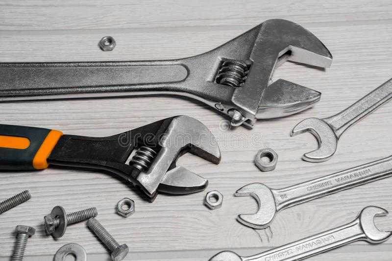 Adjustable spanners and wrenches, nuts and bolts on the table. Adjustable spanners and ordinary wrenches, nuts and bolts are on the table close up royalty free stock images