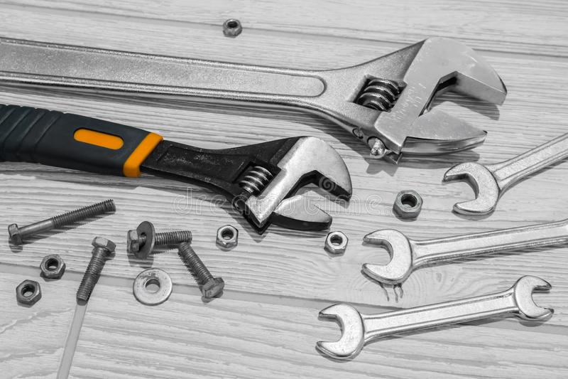Adjustable spanners and wrenches, nuts and bolts on the table. Adjustable spanners and ordinary wrenches, nuts and bolts are on the table close up royalty free stock image