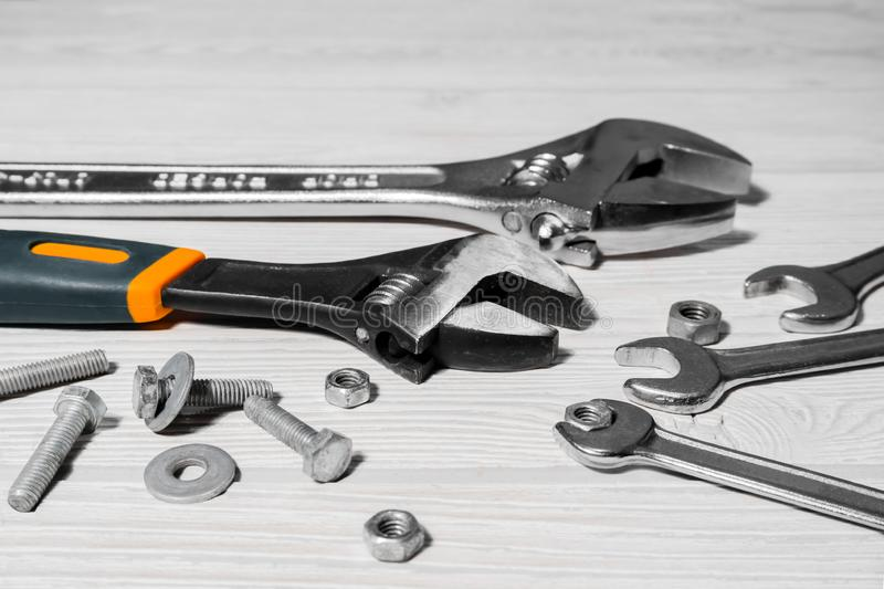 Adjustable spanners and wrenches, nuts and bolts on the table. Adjustable spanners and ordinary wrenches, nuts and bolts are on the table close up royalty free stock photo
