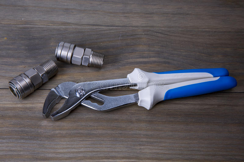 An adjustable wrench and fitting. A An adjustable wrench and fitting, on a wooden surface royalty free stock images