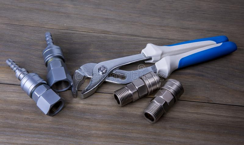 An adjustable wrench and fitting. A An adjustable wrench and fitting, on a wooden surface stock photos