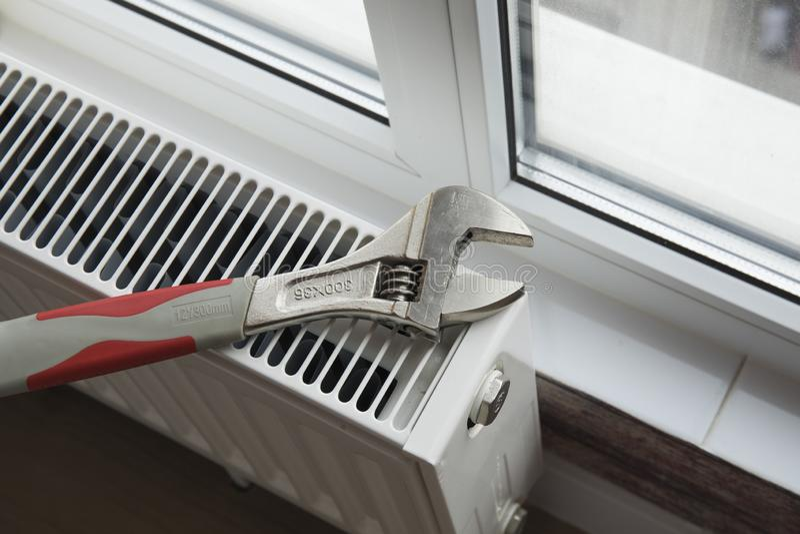 Adjustable wrench on the heating radiator stock image