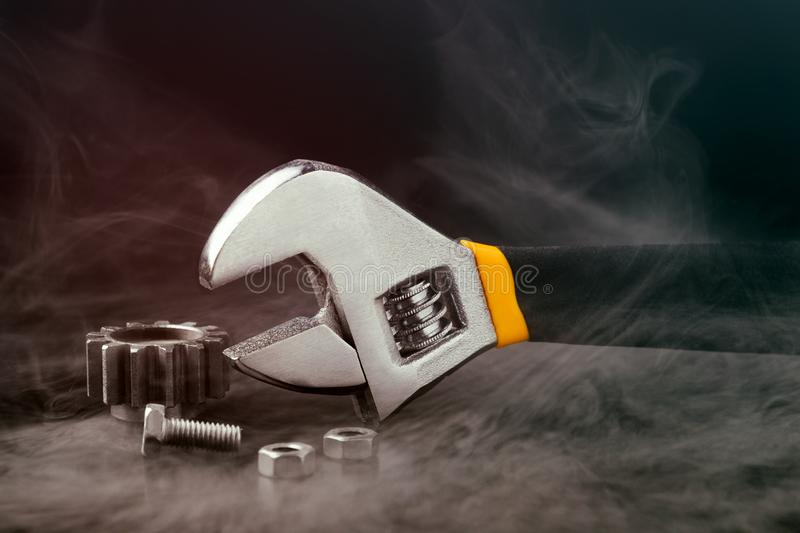 Adjustable wrench with nuts and wrapped in steam on black background. Toned light stock image