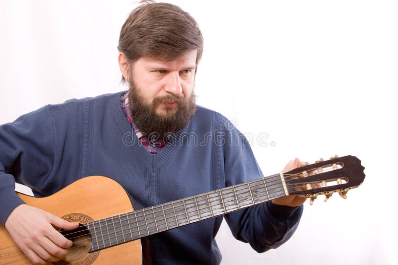 Adjusting. The man adjusting an acoustic guitar stock photography