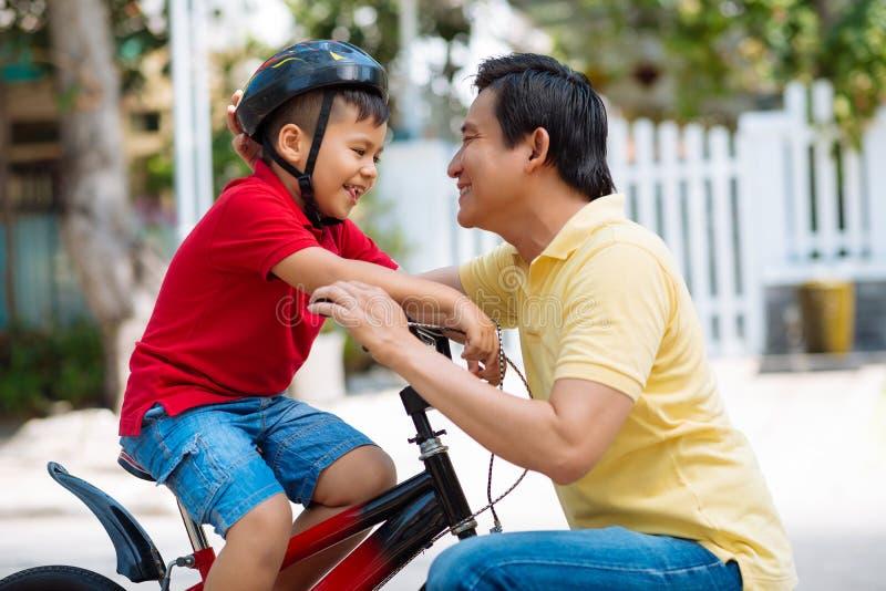 Adjusting bicycle helmet. Dad adjusting bicycle helmet of his son royalty free stock photo