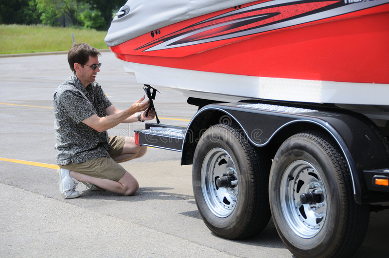 Adjusting Tie Down Straps On Boat Trailer royalty free stock photos