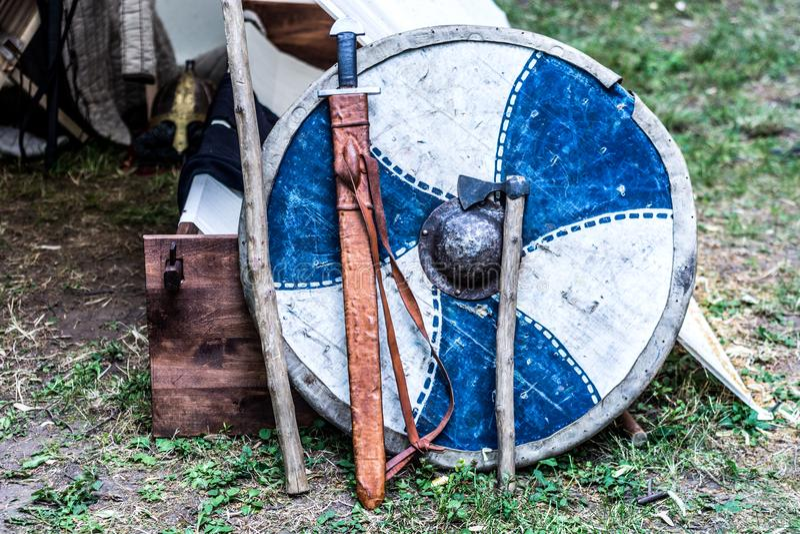 Adla skölden, svärdet och yxan framme av tältet arkivbilder