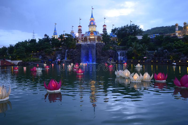 ADLABS IMAGICA ROSE FILLED POND. 13 Feb 2014; ADLABS IMAGICA; Near Lonawala; Maharashtra, India - RIDES AT THE THEME PARK, building like Moscow Russia; Rose stock image