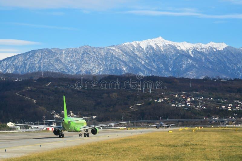 ADLER, RÚSSIA Curso Opinião do aeródromo Aeroporto internacional de Sochi Grama verde entre pistas de decolagem e montanhas bonit foto de stock royalty free