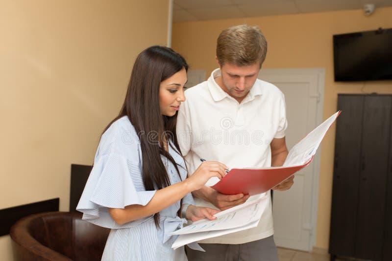 Administrador bonito da jovem mulher na recepção com o homem que olha no dobrador com papéis fotos de stock royalty free