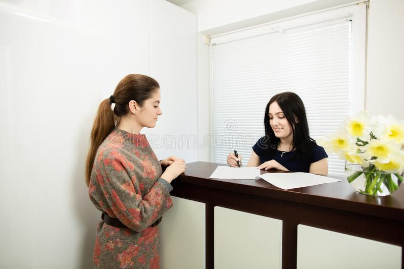 Administrador da jovem mulher em uma cl?nica dental no local de trabalho Admiss?o do cliente imagens de stock royalty free