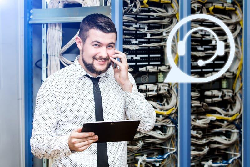 Administrador da TI no servidor com o telefone imagens de stock