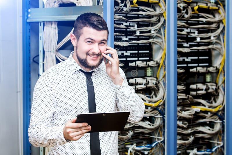Administrador da TI no servidor com o telefone imagem de stock