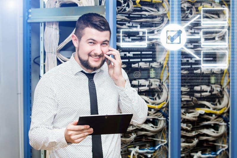 Administrador da TI no servidor com o telefone imagem de stock royalty free