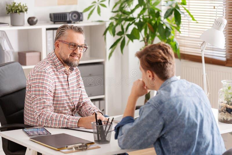 Administrador de cuentas mayor y hombre joven durante entrevista de trabajo en pequeña empresa fotos de archivo