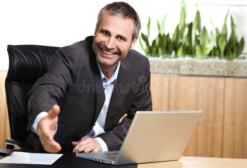 Administrador de oficinas cómodo que estira hacia fuera la mano. imagen de archivo libre de regalías