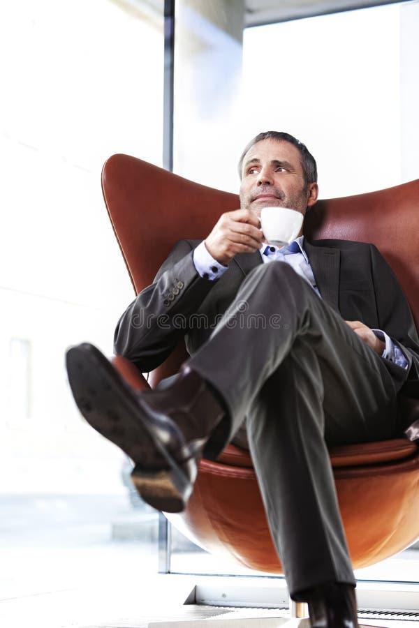Administrador de oficinas en silla roja que goza del café. fotografía de archivo