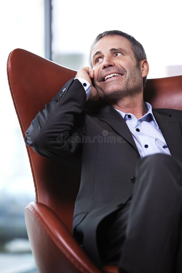 Administrador de oficinas en silla roja que habla en el teléfono celular. fotografía de archivo libre de regalías