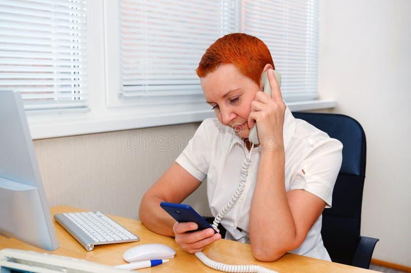 Administrador de oficinas de la muchacha linda que habla en el teléfono Sonrisas en un buen humor fotografía de archivo libre de regalías