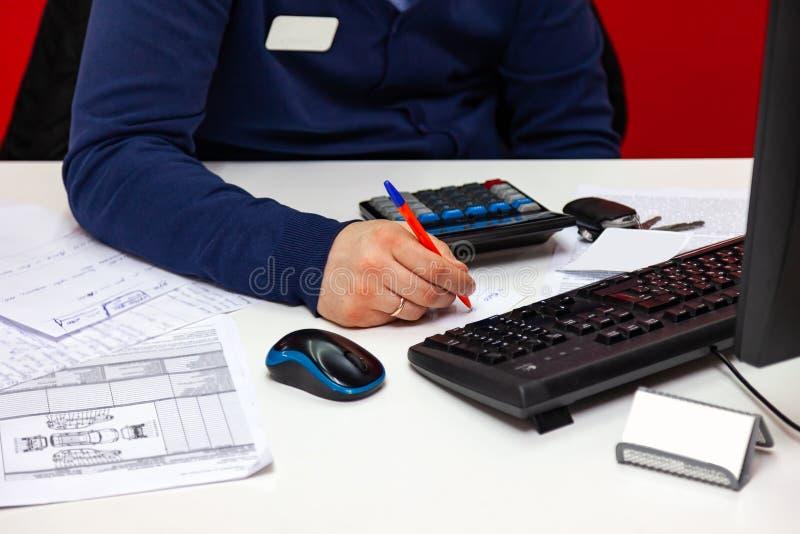 Administrador de sexo masculino joven que habla en el teléfono en el trabajo, celebrando el teléfono con su oído y al mismo tiemp imágenes de archivo libres de regalías