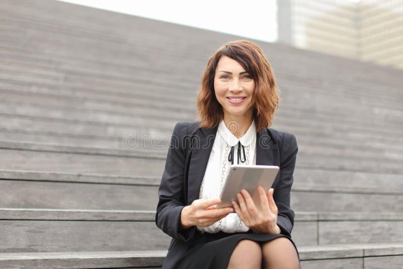 Administrador fêmea que senta-se em escadas com tabuleta e trabalho fotos de stock