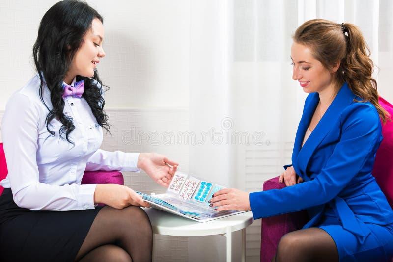 Administratören för skönhetsalongen meddelar med klienten Stående av två härliga kvinnor arkivfoton