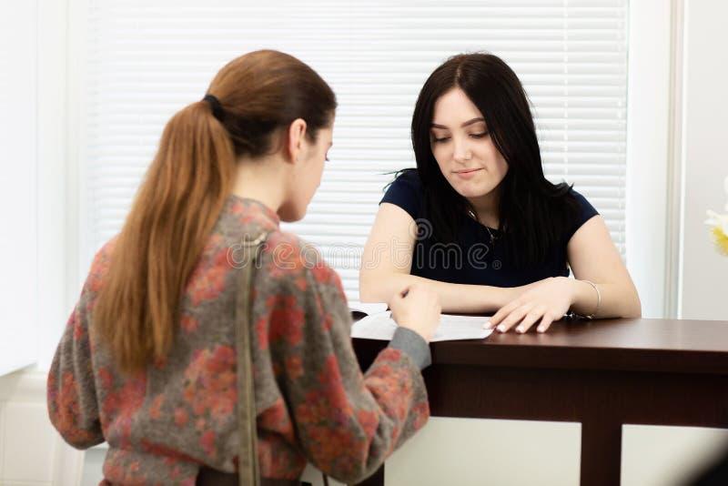 Administrat?r f?r ung kvinna i en tand- klinik i arbetsplatsen Erk?nnande av klienten royaltyfri fotografi