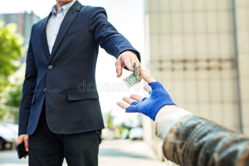 Administratieve arbeider die dollarrekening geven aan dakloze zwerver stock foto's