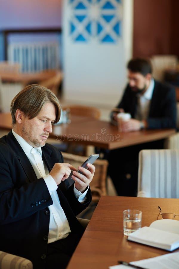 Administratieve Arbeider met Smartphone stock afbeeldingen