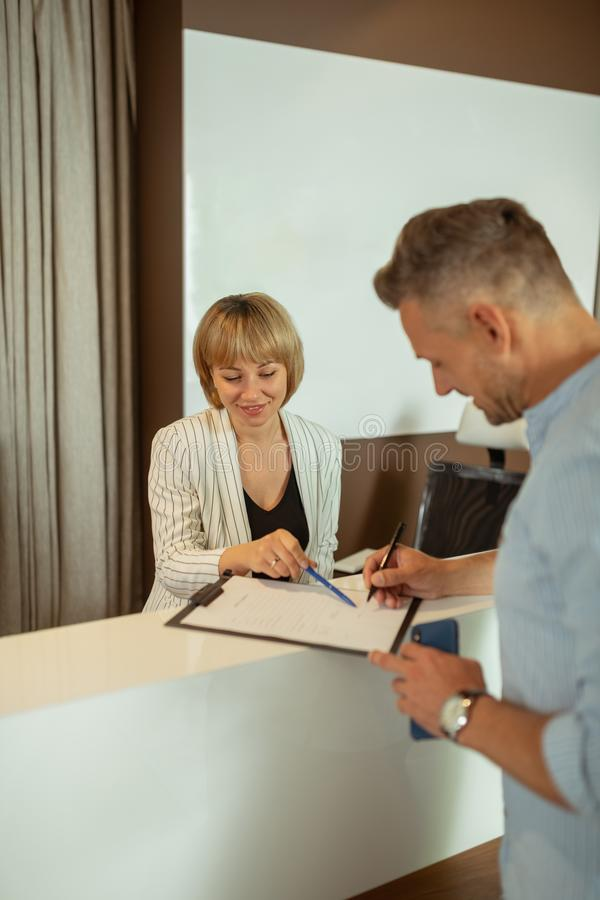 Administrator asking client to fill in the personal info form. Fill in info. Blonde-haired administrator with bob cut asking client to fill in the personal info stock images