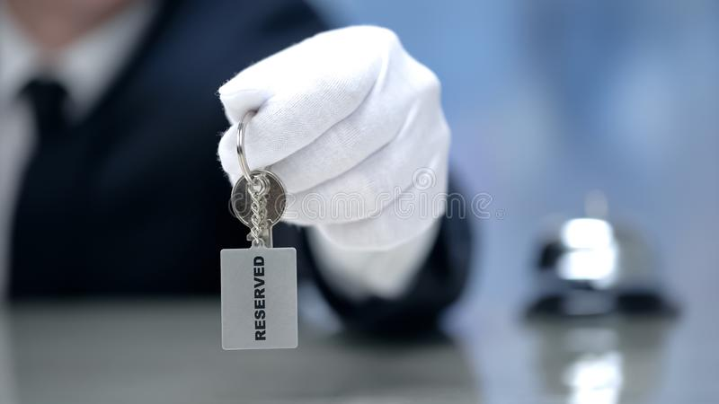 Administrator holding keys to Reserved room, luxury hotel, hospitality services. Stock photo stock images