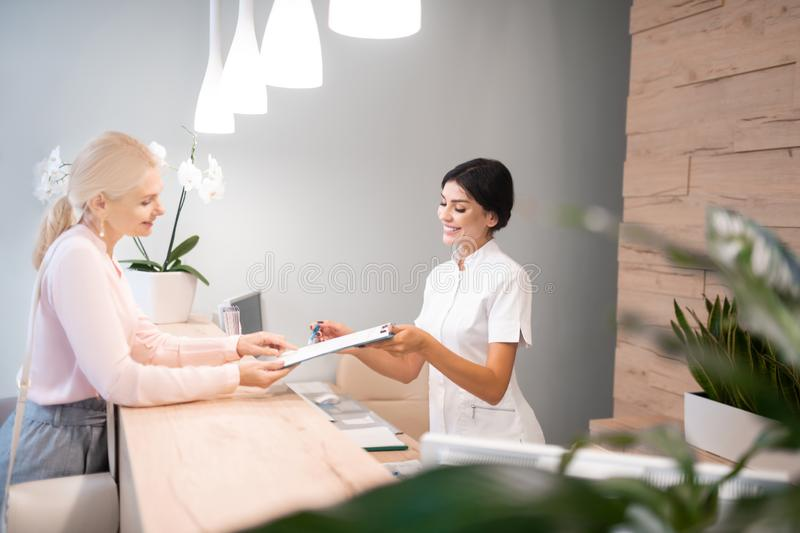 Administrator showing the client way of filling up the form. Signing papers. Cheerful administrator standing at reception desk showing the client way of filling royalty free stock photo