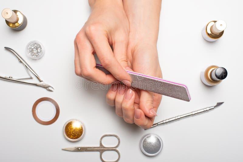 Admirablement ongles manucurés sur le bureau avec des outils pour la manucure Sur un fond blanc photos stock