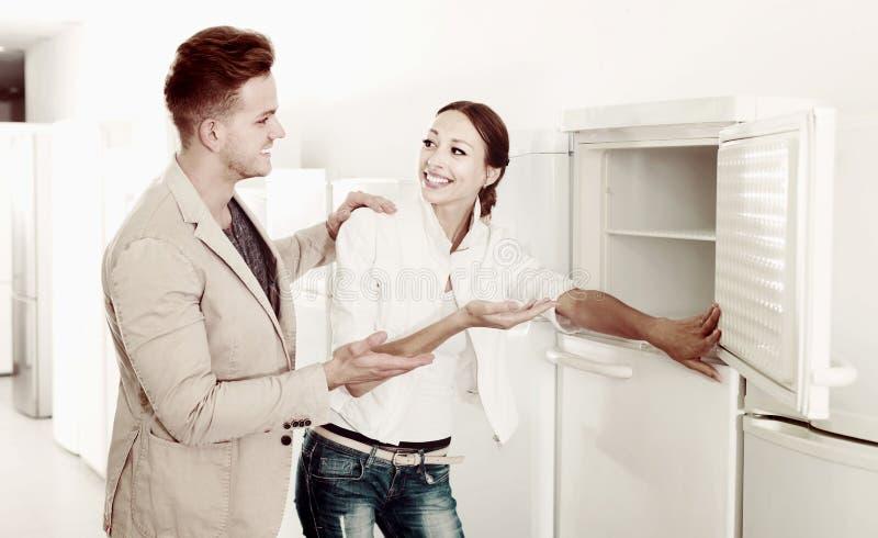 Admirando os pares que escolhem o refrigerador novo no hipermercado imagens de stock