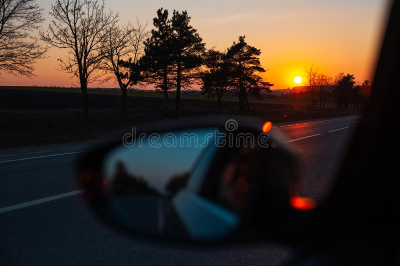 Admiring the sunset through the car window stock images