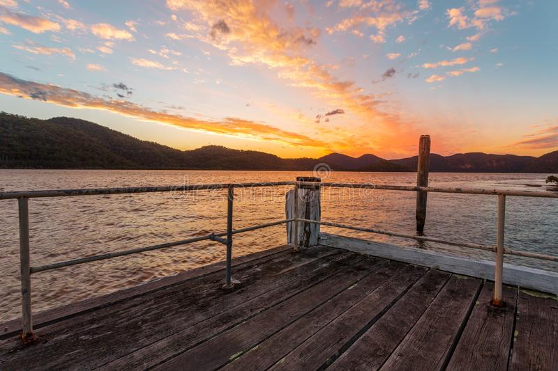Admiring the views on Peat Island Jetty sunset. Peat Island timber jetty as the sun sets behind the mountains stock photo