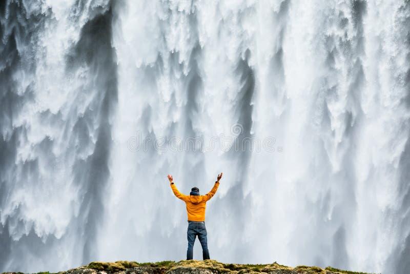 Admirnig dell'uomo la bellezza della cascata iconica di Skogafoss in Islanda fotografia stock libera da diritti