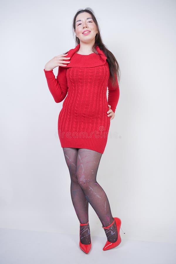 ?adna azjatykcia pyzata kobieta pozuje w czerwieni dzia? sukni? i czerni modnego pantyhose na bia?ym pracownianym tle zdjęcie stock