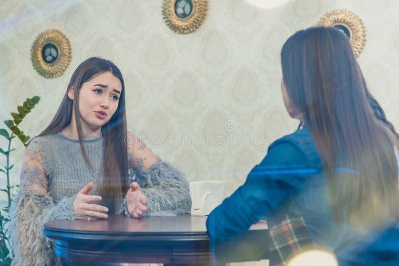 ?adny m?odej kobiety obsiadanie w kawiarni Ładny i ciepły strzał Kaukaska dziewczyna w przypadkowej odzieży przez nadokiennego sz fotografia stock