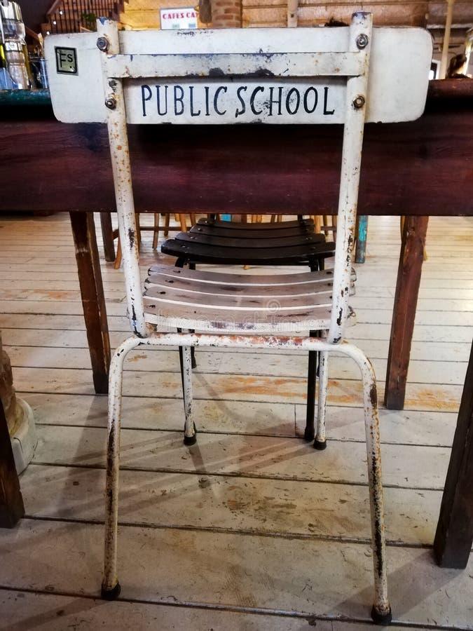 ?adny stary nauki krzes?o przed biurkiem z s?owo szko?? pa?stwow? drukuj?c? na plecy zdjęcia royalty free