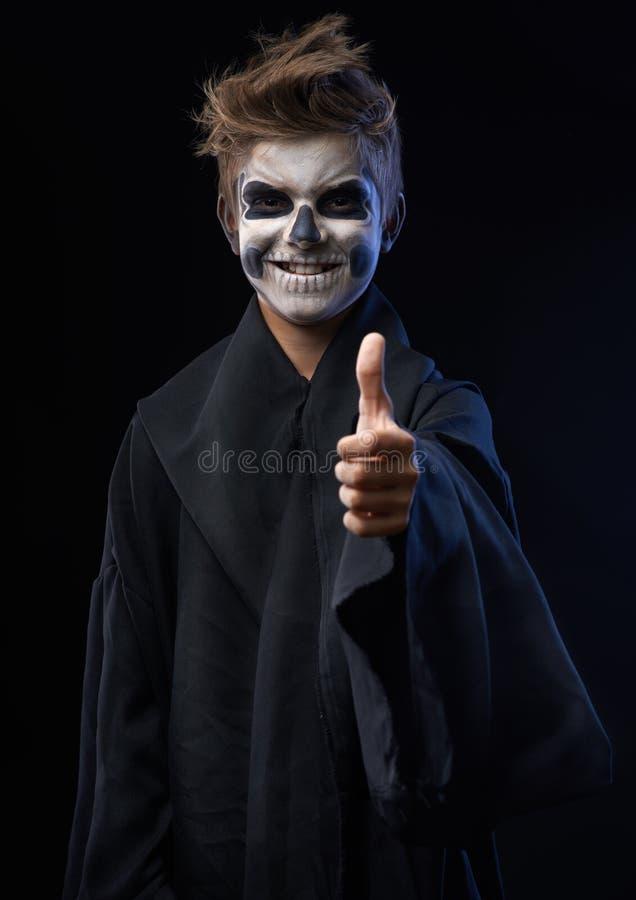 Ado avec le crâne de maquillage montrant des pouces  photographie stock libre de droits