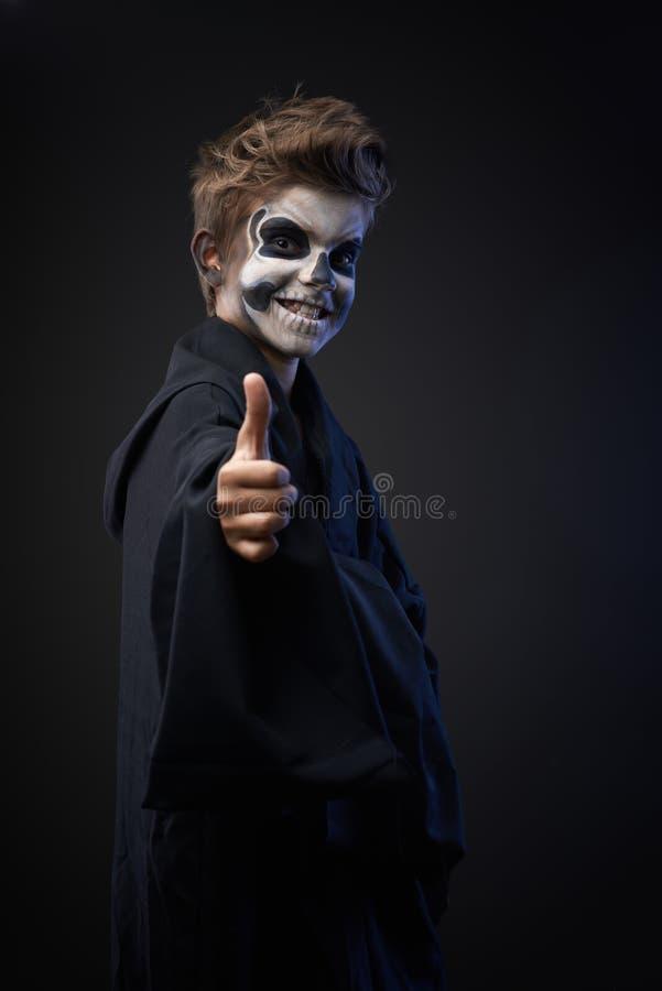 Ado avec le crâne de maquillage montrant des pouces  images stock