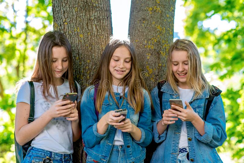 Ado d'écolière de trois filles En parc d'été par l'arbre Sur le changement d'école Dans des mains tient le smartphone Les enfants images stock