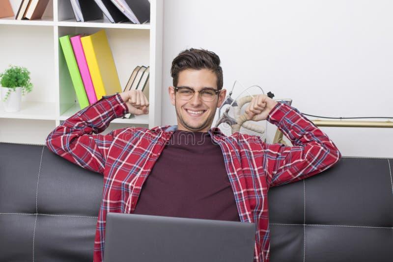 Ado de sourire s'étendant avec l'ordinateur portable images stock