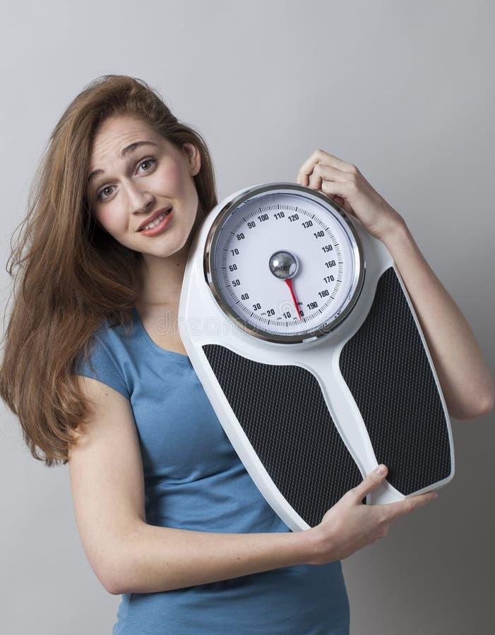Ado femelle stunned tenant son échelle de poids pour vérifier la surveillance du poids photo libre de droits