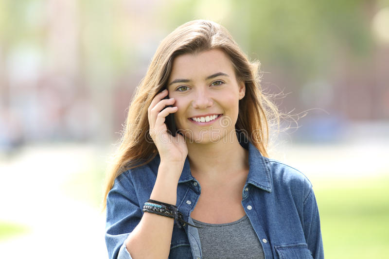 Ado marchant et invitant le téléphone vous regardant image libre de droits