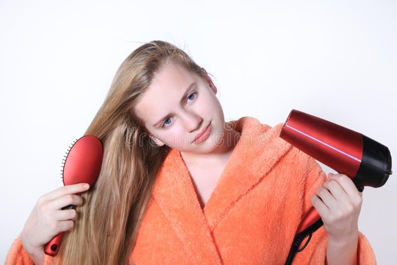 Ado se peignant les cheveux utilisant un hairdryer pour sécher photo stock