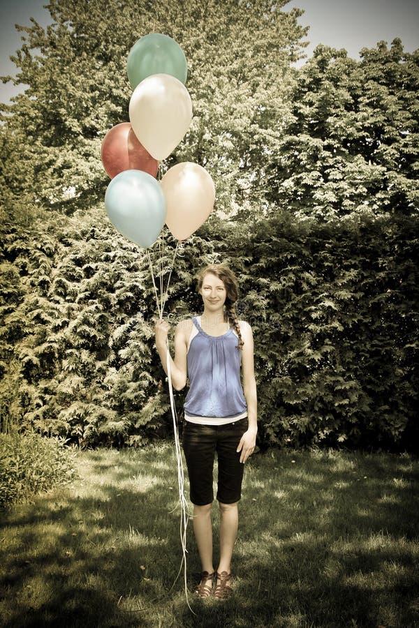 Ado tenant des ballons image stock